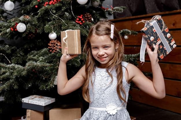 Bambino felice che cerca di indovinare cosa c'è dentro le sue scatole regalo. ragazza seduta sul pavimento in un accogliente soggiorno decorato.
