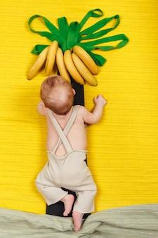 Il bambino felice vuole avere la frutta della banana. palma con banane in crescita