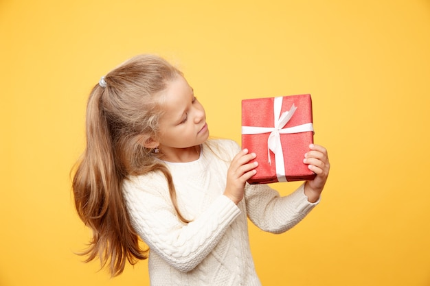 Bambino felice con regalo isolato su sfondo giallo