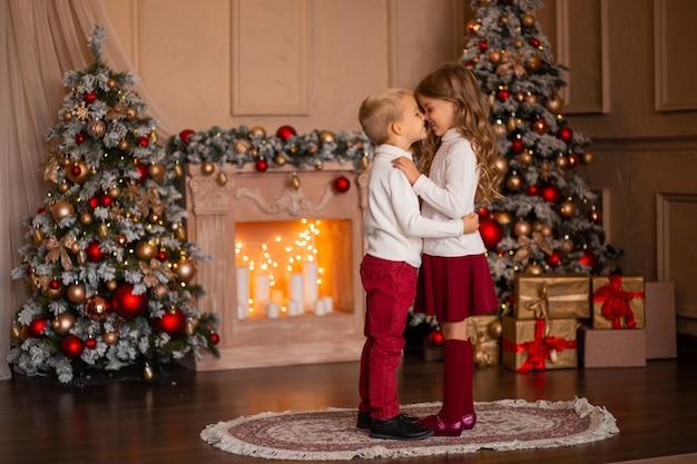 Bambini felici fratello e sorella sullo sfondo del camino e albero di natale a luci