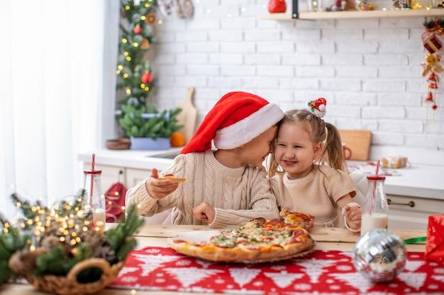 Bambini felici fratello e sorella che mangiano pizza in cucina
