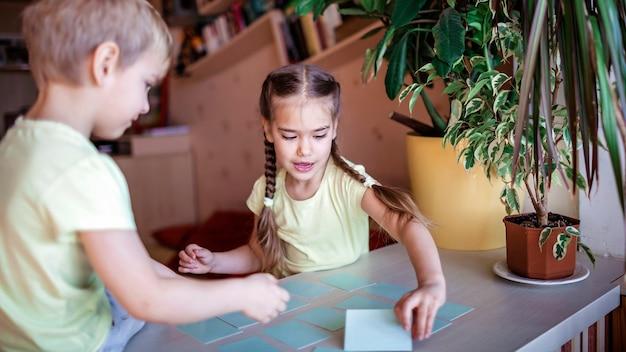 Bambini felici che giocano al memo del gioco da tavolo negli interni domestici, i valori della famiglia in realtà, stanno a casa, la vita durante la quarantena