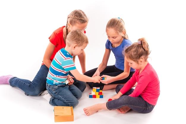 Bambini felici che giocano con le particelle elementari isolate su bianco. lavoro di squadra, concetto di creatività.