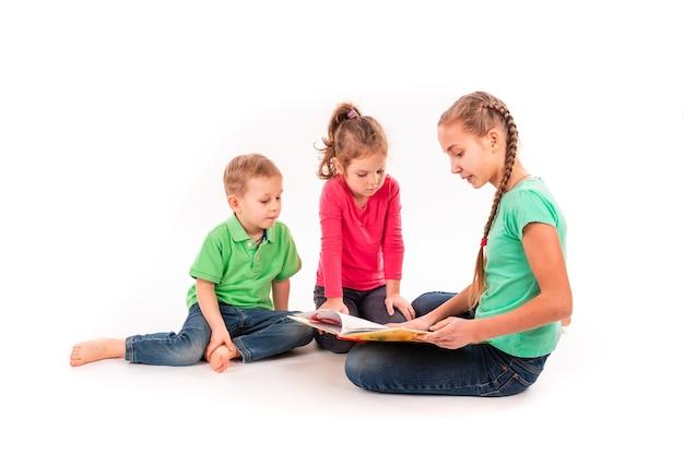 Bambini felici che leggono un libro isolato su bianco. lavoro di squadra, concetto di creatività.