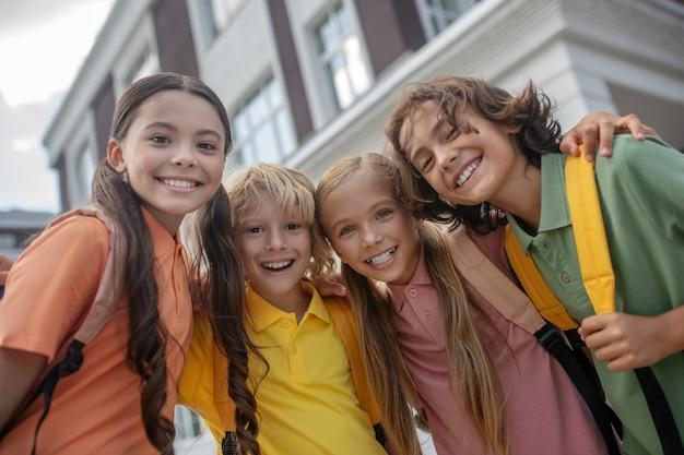 Bambini felici. scolari in piedi nel cortile della scuola e che sembrano allegri