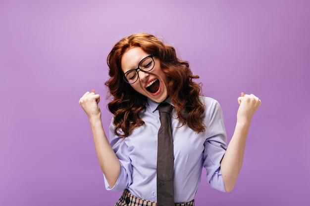 Happy lady in abito stile business posa emotivamente sul muro viola