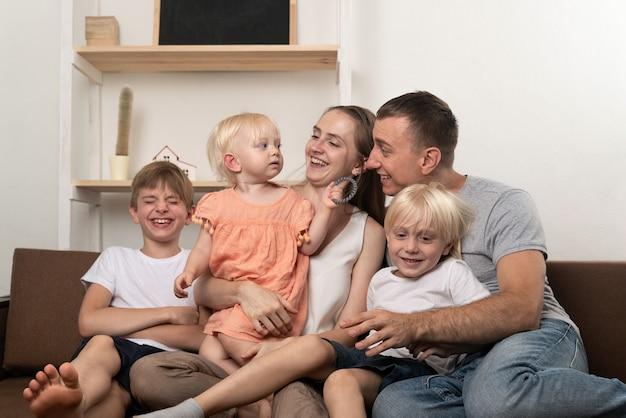 Famiglia numerosa felice a casa. i genitori e tre bambini piccoli sono divertenti.