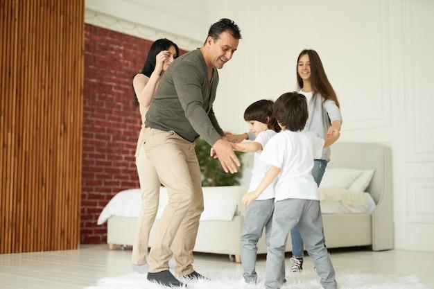 Famiglia latina felice che si diverte al chiuso. mamma e papà giocano con i loro bambini a casa. famiglia, concetto di genitorialità