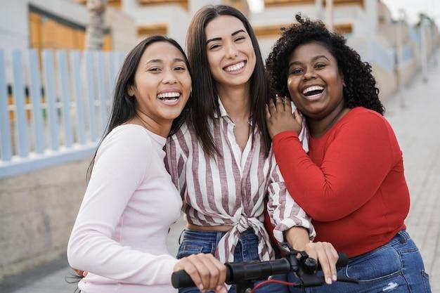 Ragazze latine felici che si divertono con lo scooter elettrico all'aperto in città - obiettivo principale sul volto della donna centrale