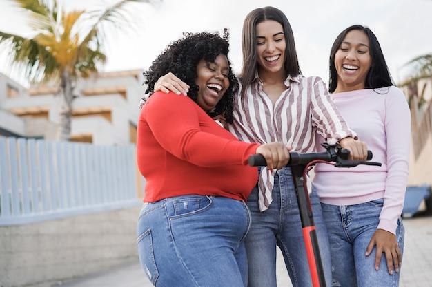 Ragazze latine felici che si divertono con lo scooter elettrico all'aperto in città