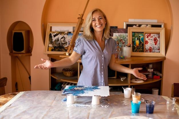 L'artista ridente felice è felice di invitarci a fare pittura d'interni con lei. felicità e creatività. pittura in interni.hobby e artigianato. imparare a disegnare. lavoro a casa. stile di vita.