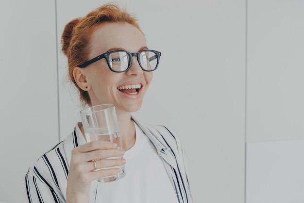 Felice donna zenzero ridente in piedi in cucina al mattino con un bicchiere di acqua minerale pura