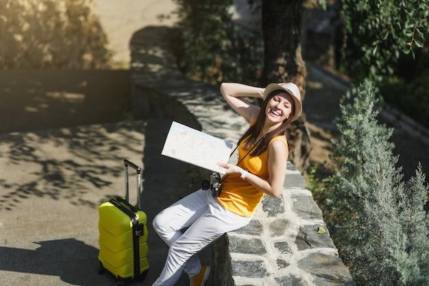 Donna turistica del viaggiatore di risata felice in cappello giallo dei vestiti con la mappa della città della valigia che si siede sulla pietra nel parco della città all'aperto. ragazza che viaggia all'estero per viaggiare nel fine settimana. stile di vita del viaggio turistico.