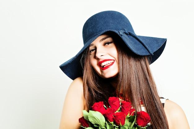 Donna che ride felice con rose rosse