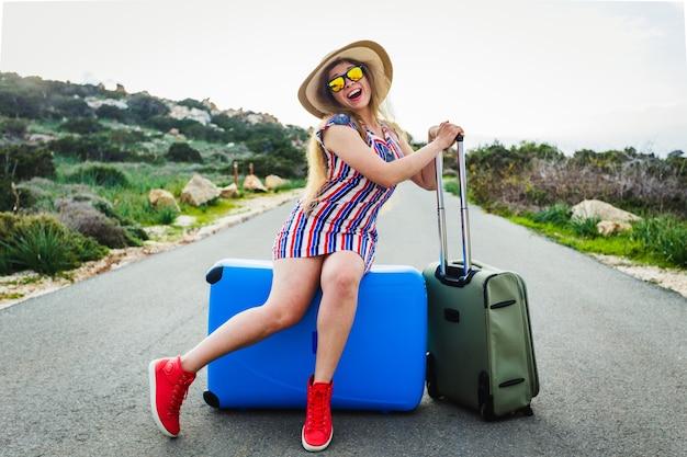 Felice ridendo giovane donna in attesa seduta sulla valigia sulla strada.