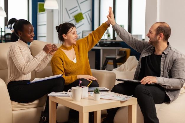 Il leader felice motiva i diversi dipendenti il team aziendale dà il cinque insieme, il gruppo di impiegati eccitati e l'allenatore impegnati nel teambuilding celebrano il successo i buoni risultati ricompensano nel concetto di lavoro di squadra