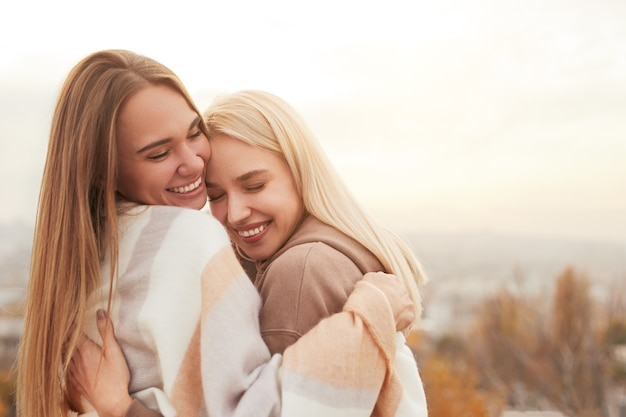 Coppie lesbiche felici che abbracciano nella campagna