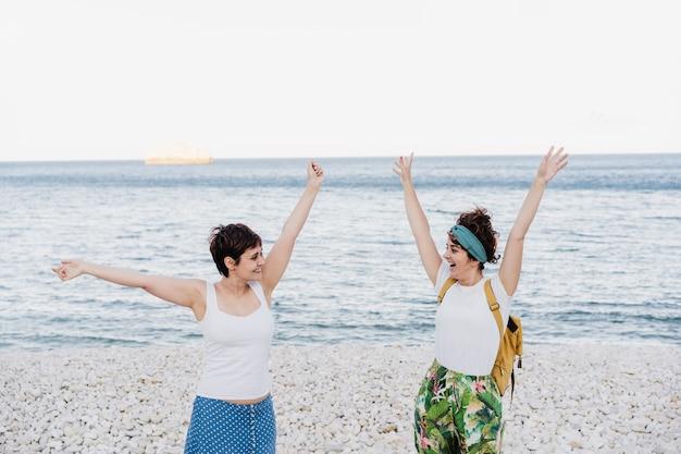 Felice coppia lesbica con le braccia alzate di felicità in spiaggia durante il tramonto. l'amore è amore e concetto lgtbi