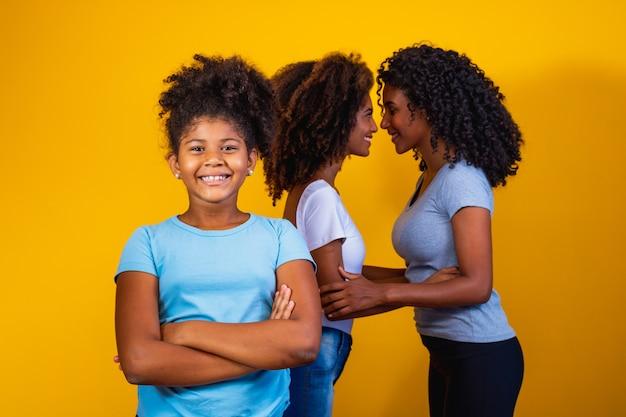 Felice coppia lesbica con bambino su sfondo giallo. coppia insieme alla figlia adottiva, concetto di adozione