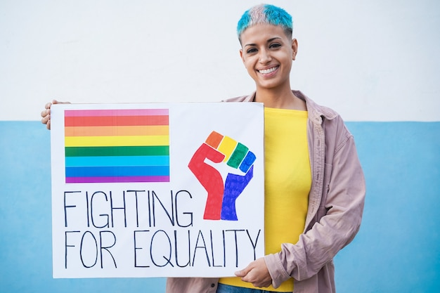 Felice donna lesbica alla parata del gay pride che tiene la bandiera lgbt