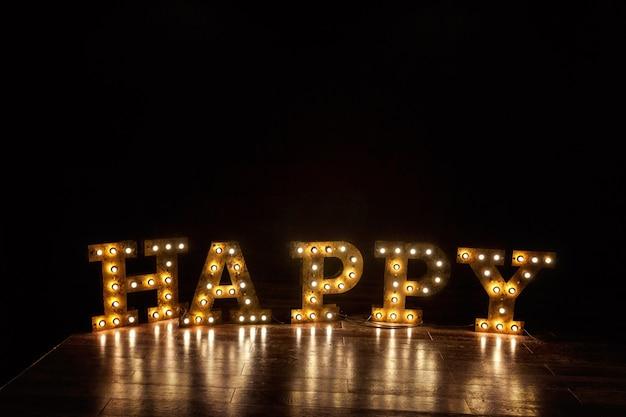 Lettere felici parola luce incandescente lampadine retrò in piedi sul pavimento. appartamento di design d'interni in stile classico scuro moderno con sfondo di lampadine di lampade retrò