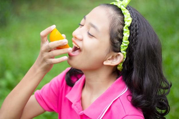 Piccola ragazza asiatica felice che mangia arancia nel giardino.
