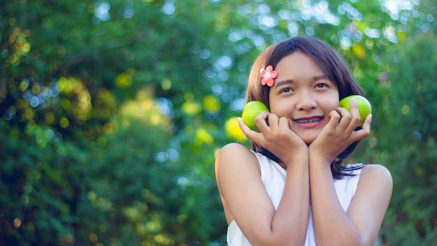 Felice piccola ragazza asiatica tenere ogreen appel in mano indossa un abito bianco