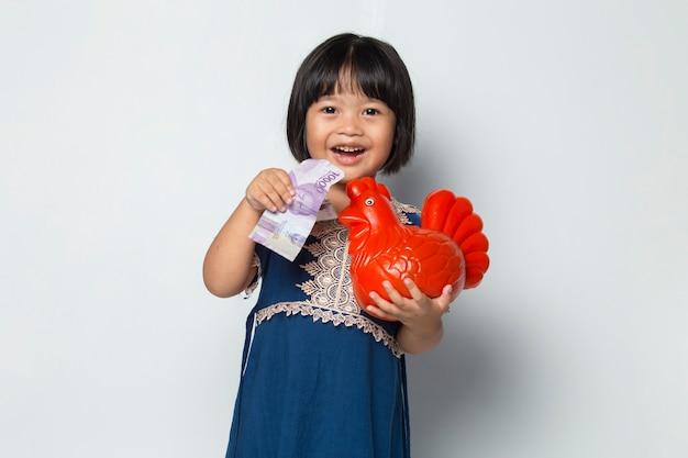 Felice piccola ragazza asiatica che risparmia denaro con una banca di pollo isolata su sfondo bianco