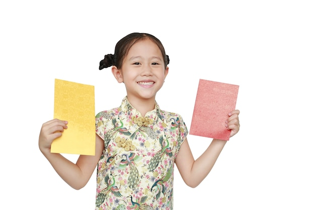 Felice bambina asiatica che indossa cheongsam sorridente e in possesso di busta d'oro e rossa su sfondo bianco.