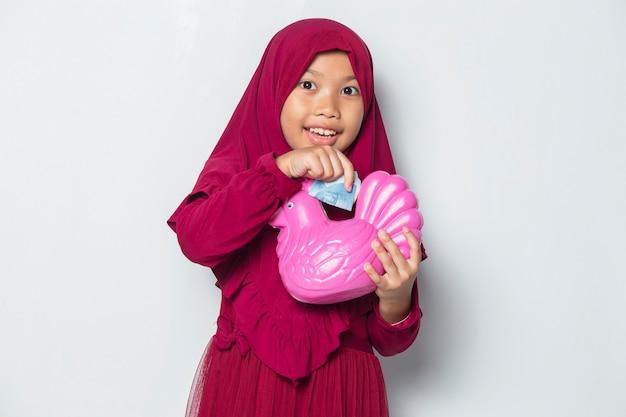 Felice piccola ragazza musulmana asiatica risparmiare denaro con una banca di pollo isolata su sfondo bianco