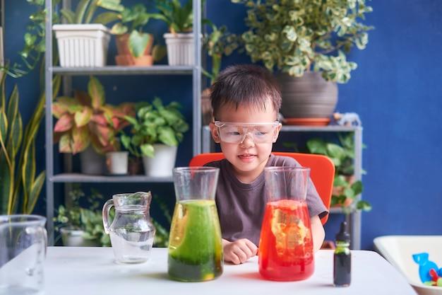 Felice ragazzino asiatico della scuola che studia scienze, facendo esperimenti scientifici con lampada lava fai-da-te con olio, acqua e colorante alimentare