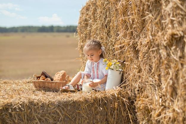Piccolo bambino felice in abiti popolari si siede su un campo di grano con un barattolo di latte fresco.