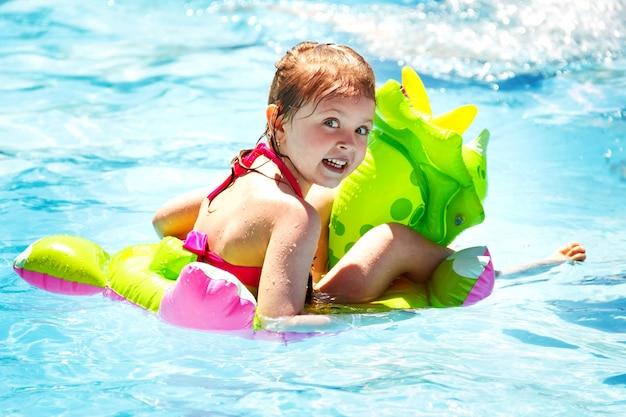 Bambina felice che ride in piscina su un dinosauro gonfiabile in estate