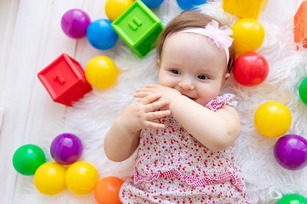 Piccola neonata felice con i giocattoli colorati
