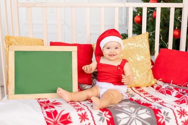 Felice piccolo bambino sei mesi in un cappello da babbo natale seduto in una culla a casa dall'albero di natale con una scheda di testo, il nuovo anno e il concetto di vacanza