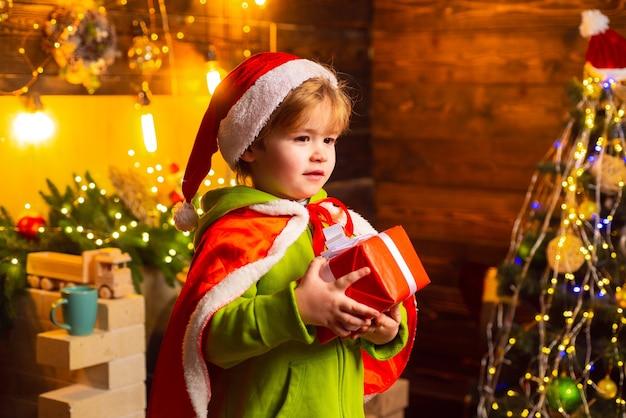 Ragazzino felice vicino all'albero di natale con il suo regalo di natale. il ragazzino indossa i vestiti di babbo natale. concetto di natale.