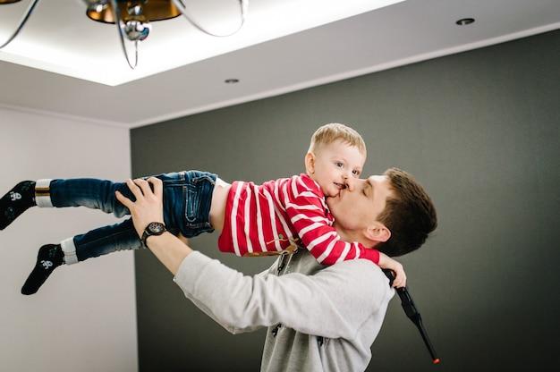 Felice ragazzino e papà in maglioni di babbo natale giocano e celebrano il natale