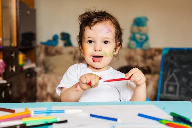 Il ragazzino felice disegna con pennarelli colorati su un pezzo di carta