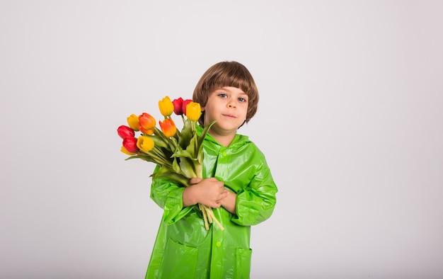 Un ragazzino felice con un impermeabile verde tiene un mazzo di tulipani colorati su uno sfondo bianco con un posto per il testo