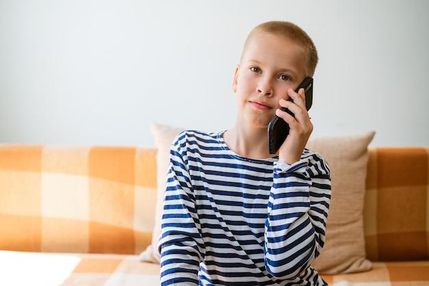 Felice ragazzino che si diverte a giocare sul cellulare bambino in età prescolare seduto sul divano con un sorriso