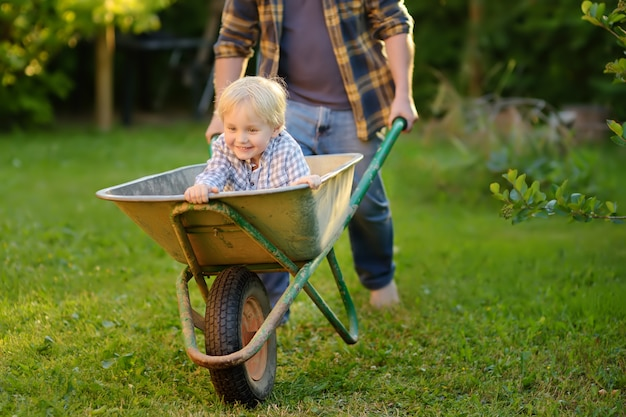 Ragazzino felice divertendosi in una carriola che spinge dal papà in giardino domestico il giorno soleggiato caldo.