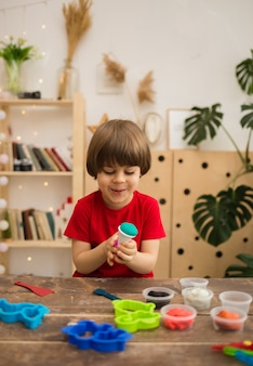 Il ragazzino felice sta giocando con la plastilina e gli stampi a un tavolo nella stanza