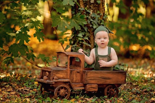 Ragazzino felice che si siede nell'automobile del giocattolo dei bambini di legno all'aperto in estate.