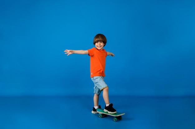 Il ragazzino felice sta con uno skateboard su una superficie blu con spazio per il testo