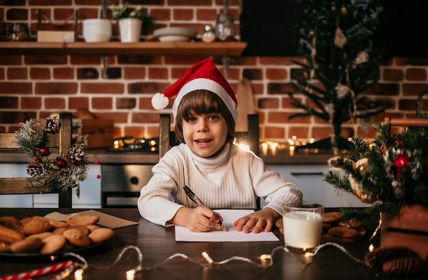 Un ragazzino felice con un maglione bianco a maglia e un cappello rosso scrive una lettera di capodanno