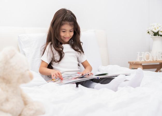 Felice piccola ragazza bruna seduta sul letto a casa leggendo un libro.