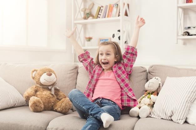 Felice bambina casual guardando la tv a casa. eccitata bambina seduta sul divano con i suoi amici giocattolo orsacchiotto e pecore, godendosi il cartone animato preferito, copia spazio