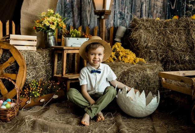 Piccolo ragazzo caucasico felice che si siede su una paglia con un guscio con gli anatroccoli. pasqua per i bambini