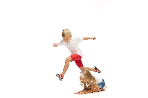 Felice piccola ragazza caucasica e ragazzo che saltano e corrono isolati su sfondo bianco