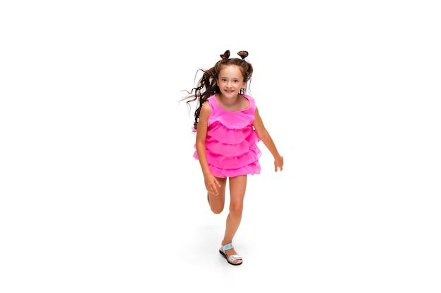 Felice piccola ragazza caucasica che salta e corre isolata su sfondo bianco
